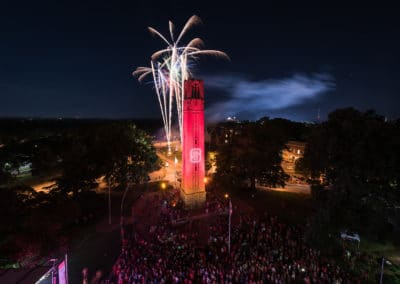 NC State's Belltower lit red.